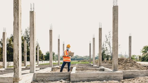 Ingenieur man gebruik laptop en werk industrie project check huisplan ontwerp op bouwplaats