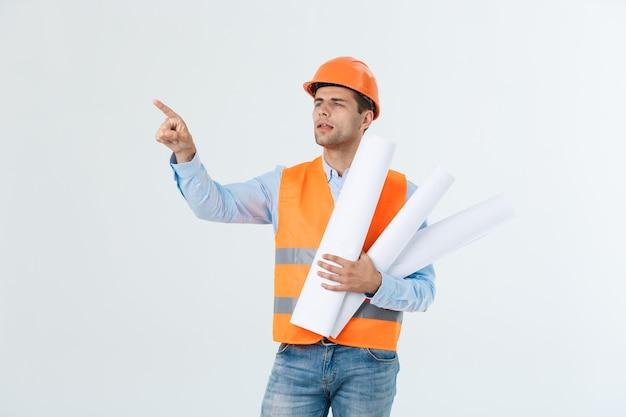 Ingenieur man in de oranje helm wijst met zijn vinger om ruimte te kopiëren.