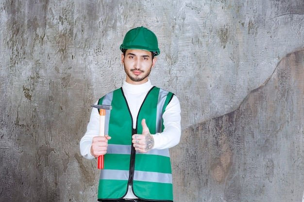 Ingenieur man in geel uniform en helm die een houten bijl vasthoudt voor reparatie en plezier handteken toont