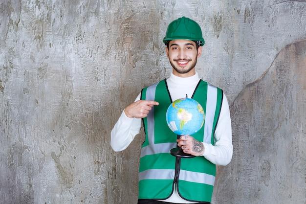 Ingenieur man in geel uniform en helm die een wereldbol vasthoudt en er plaatsen overheen zoekt.