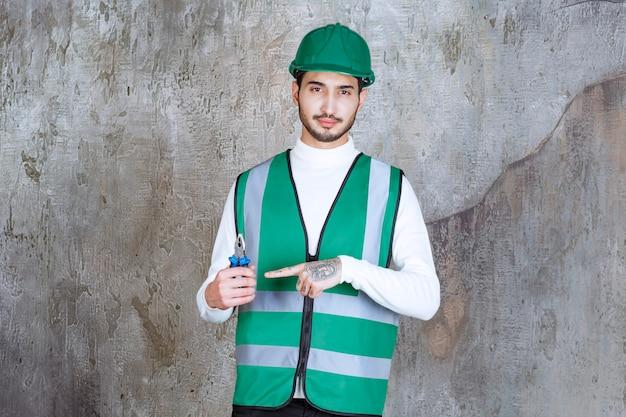 Ingenieur man in geel uniform en helm met blauwe tang voor reparatie.