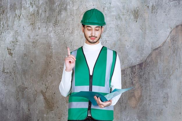 Ingenieur man in geel uniform en helm met een blauwe map en hand opsteken voor aandacht.