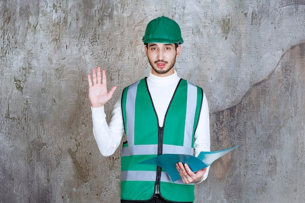Ingenieur man in geel uniform en helm met een blauwe map en iets tegenhouden.