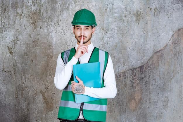 Ingenieur man in geel uniform en helm met een blauwe map en vraagt om stilte.