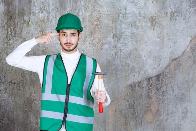 Ingenieur man in geel uniform en helm met een houten bijl voor reparatie en ziet er attent uit
