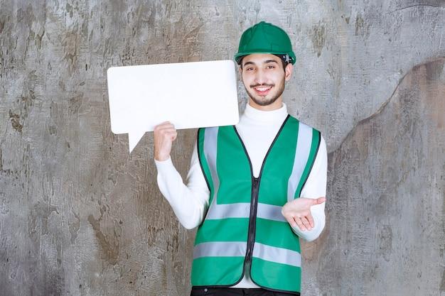 Ingenieur man in geel uniform en helm met een leeg infobord