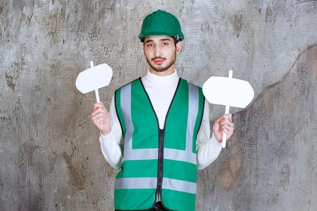 Ingenieur man in geel uniform en helm met infoborden in beide handen.