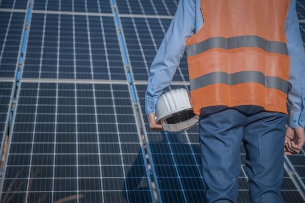 Ingenieur, man in uniform en masker, helmbril en werkjas op een achtergrond van zonnepanelen bij zonnestation. technicus controleert het onderhoud.