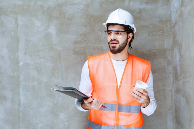 Ingenieur man in witte helm en beschermende bril met een zwarte map en een kopje drank.