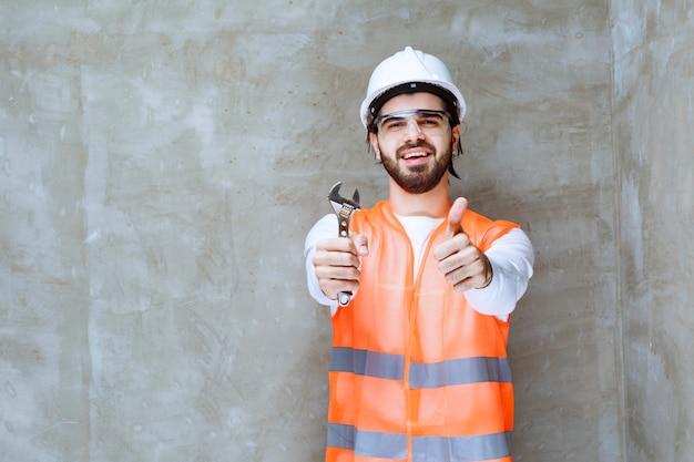 Ingenieur man in witte helm en beschermende bril met metalen moersleutels en plezier teken tonen.