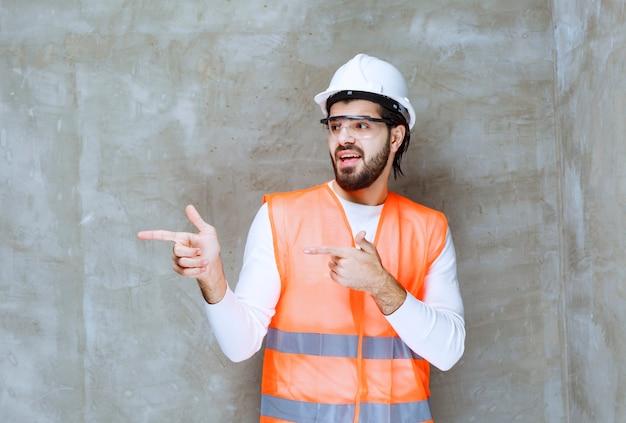 Ingenieur man in witte helm en beschermende bril wijzend op zijn collega of op iets terzijde.