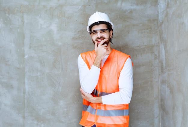 Ingenieur man in witte helm en beschermende bril ziet er verward en attent uit.