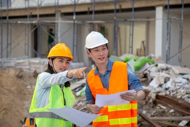 Ingenieur-manager inspecteert bouwplaatsen en controleert blauwdrukken bij het bouwen van stadshuisproject