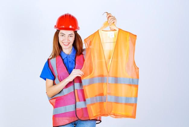 Ingenieur meisje in uniform presenteert een stuk veiligheidsvest aan de collega.