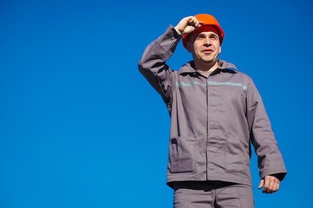 Ingenieur met beschermende helmstandaard buitenshuis