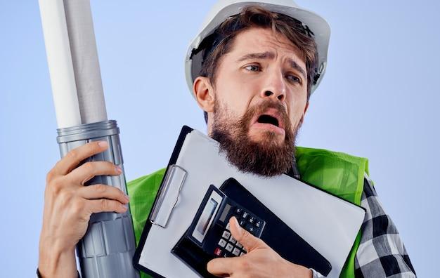 Ingenieur met blauwdrukken in handen bouw beroep blauwe muur.
