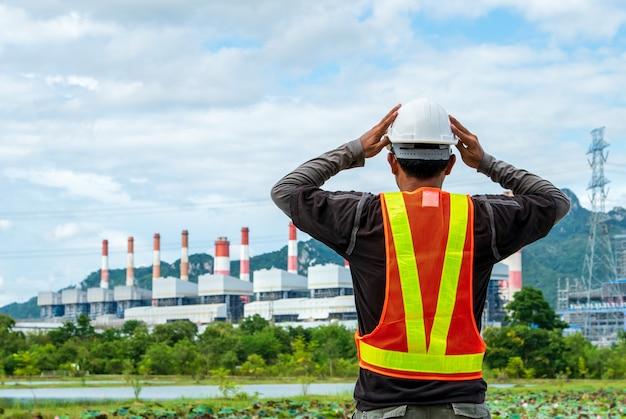 Ingenieur met een steenkoolelektrische centrale op de achtergrond, thailand.