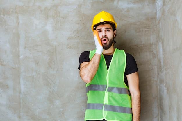 Ingenieur met geel masker en industriële handschoenen ziet er verward en doodsbang uit