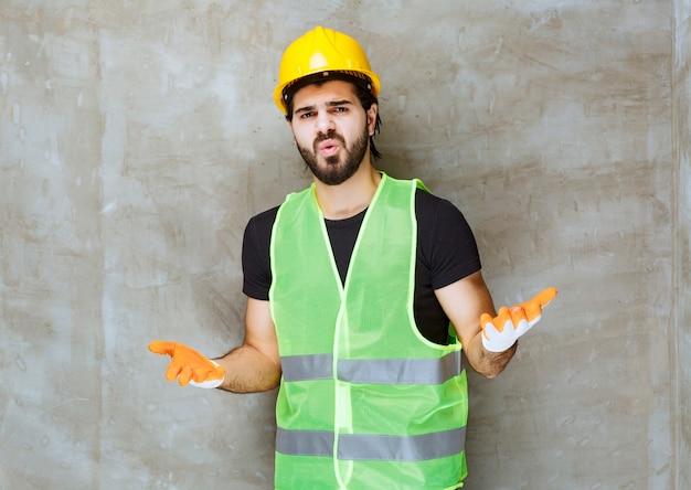 Ingenieur met geel masker en industriële handschoenen ziet er verward en doodsbang uit Gratis Foto