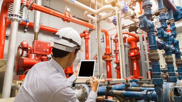 Ingenieur met tabletcontrole rode generatorpomp voor watersprinklerleidingen en brandalarmregelsysteem.