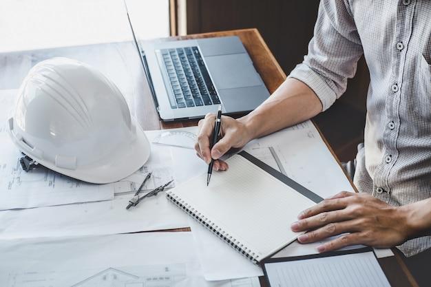Ingenieur of architect die aan blauwdruk werken, ingenieur die met techniekhulpmiddelen werken