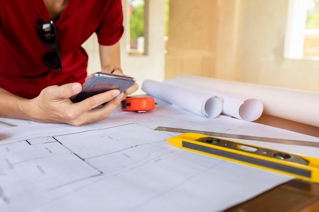 Ingenieur of architect die celtelefoon in bouwconstructieplaats met behulp van.