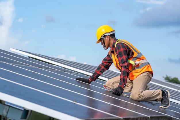 Ingenieur of elektricien controleren en onderhouden van vervangend zonnepaneel bij zonne-energiecentrale, groene energie en duurzame ontwikkeling voor zonne-energiegenerator.