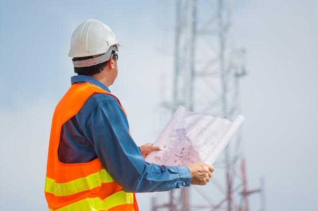 Ingenieur of technocian houdt plan vast en kijkt naar telecommunicatietorenbasis