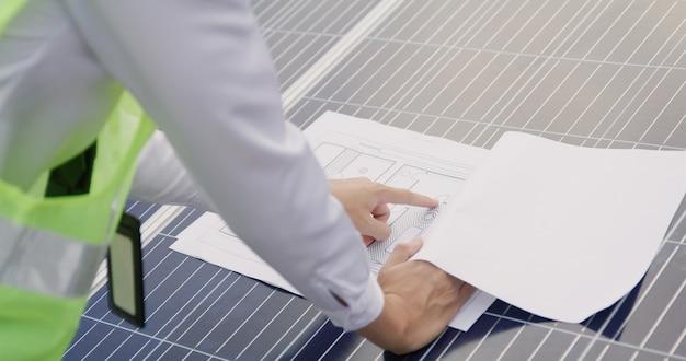 Ingenieur open blauwdruk van zonneboerderijproject op samenvattend rapport van zonnecellen, technologie en groen ecologie-energiesysteemconcept.