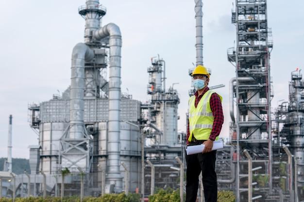 Ingenieur raffinaderijindustrie die co-beschermende coronavirusziekte draagt vanaf 2019 of covid-19mask verdrietig vanwege werkloosheid