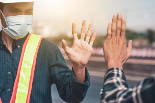 Ingenieur schud de hand nieuwe normale sociale afstand