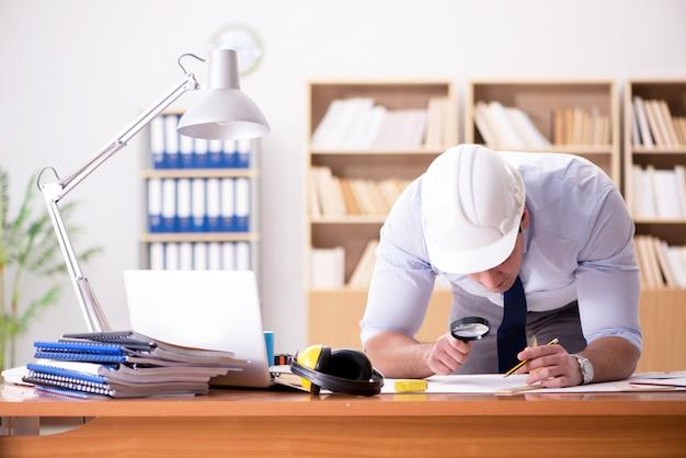Ingenieur supervisor werkt aan tekeningen op kantoor