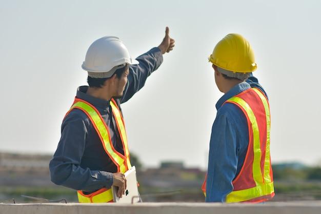 Ingenieur twee mensen staken hun hand op bij sky sun light, supervisor foreman construction