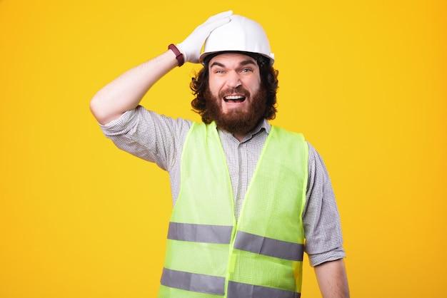 Ingenieur vergat iets te doen, gezichtsuitdrukking van constructeur met helm