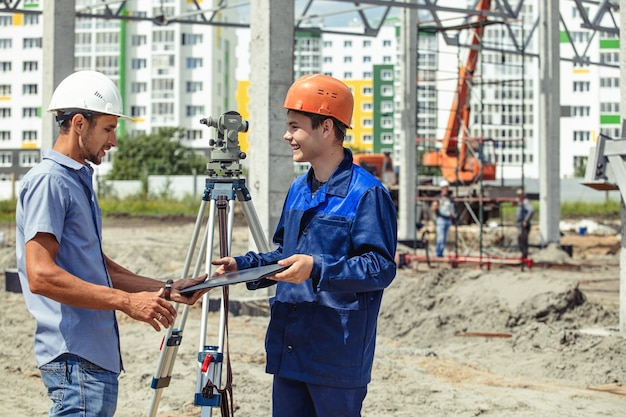 Ingenieur voorman geeft orders aan arbeiders en bouwers die een gebouw op de bouwplaats bouwen