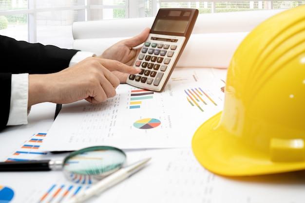 Ingenieur werkende projectboekhouding met calculator en grafiek.
