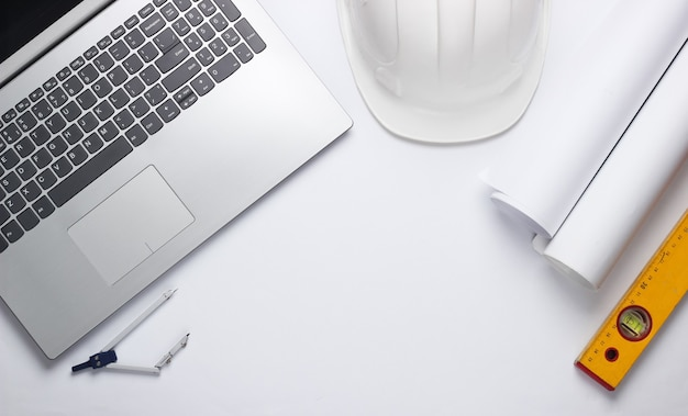 Ingenieur werkruimte. laptop, rollen tekeningen, toolson witte achtergrond. bovenaanzicht. kopieer ruimte