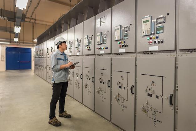 Ingenieur werkt en controleert de elektrische energieverdeling van de statusschakelapparatuur bij onderstationruimte