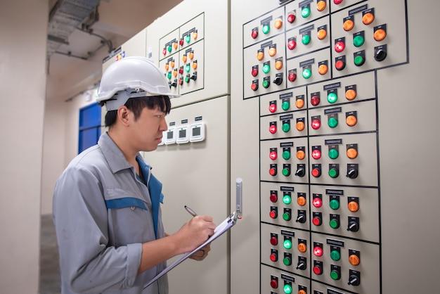 Ingenieur werkt en controleert status elektrisch paneel bij hvac-kamer