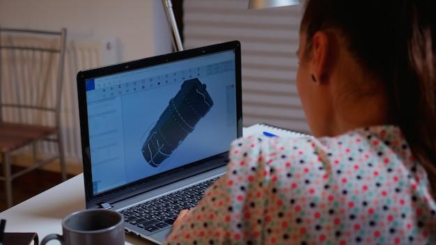 Ingenieur werkt 's avonds laat aan een 3d-model van industriële turbine vanuit huis. externe freelancer die prototype-idee bestudeert op pc met cad-software op het scherm van het apparaat