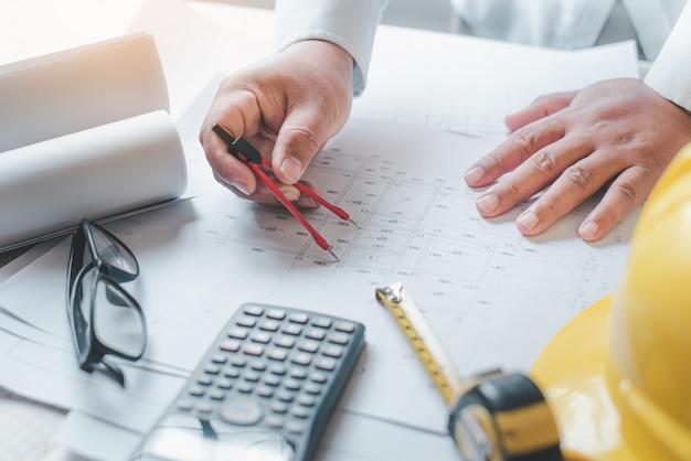 Ingenieur werkzaam in kantoor met blauwdrukken