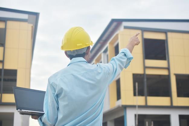 Ingenieur wijzend op de bouwplaats