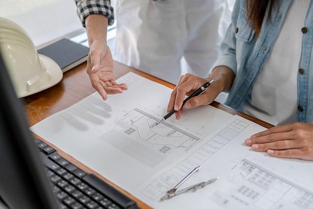 Ingenieurs bespreken een blauwdruk tijdens het controleren van informatie op een tabletcomputer in een kantoor.
