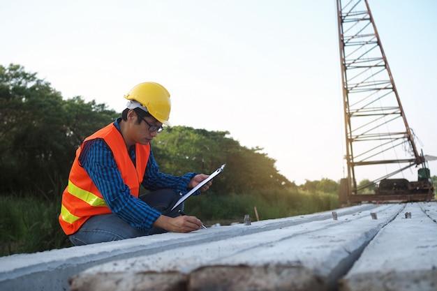 Ingenieurs controleren de palen die in het bouwgebied zijn geplaatst en de achterkant heeft kranen.