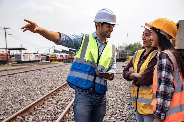 Ingenieurs die aan het treinstation werken en een laptop vasthouden