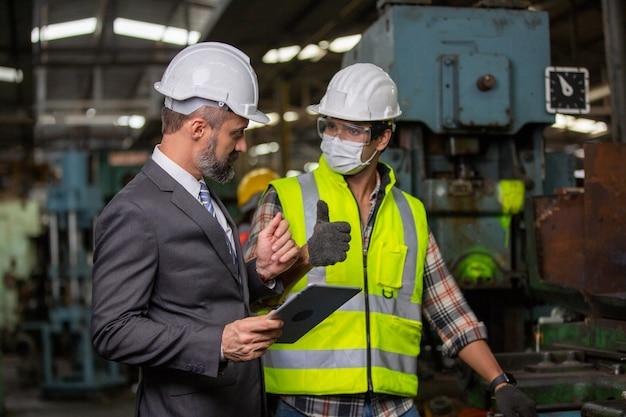 Ingenieurs die een cnc-machine in de fabriek bedienen