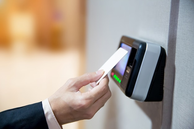 Ingenieurs die een sleutelkaart gebruiken om hun identiteit te verifiëren voor toegang tot de deur.