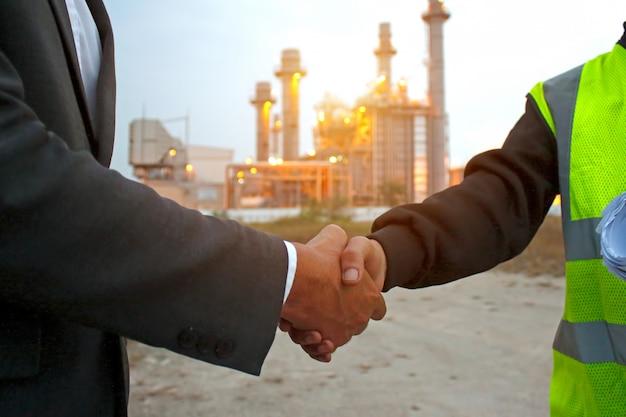 Ingenieurs die handen bij krachtcentrale schudden na succesdag