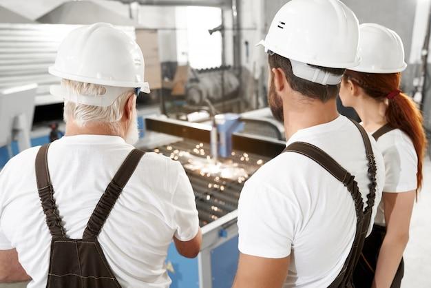 Ingenieurs die plasma lasersnijdend metaal waarnemen.