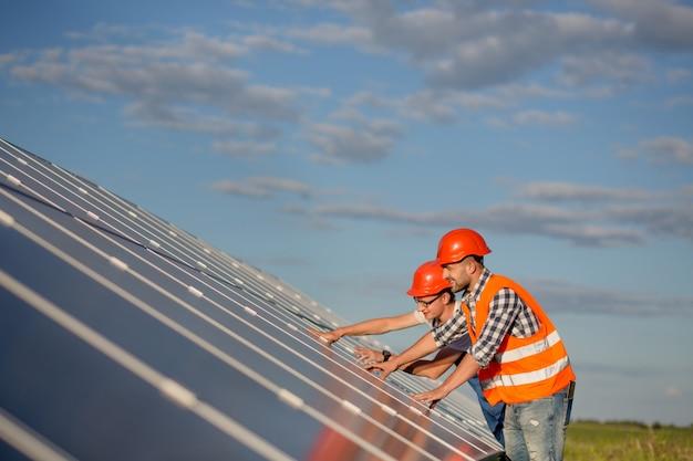 Ingenieurs die zonnepanelen in het veld onderhouden.